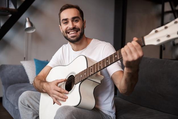 Foto des europäischen mannes 30s, der lässiges t-shirt spielt, das akustische gitarre spielt, während auf sofa in wohnung sitzt