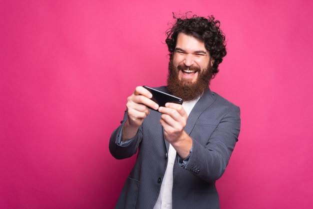 Foto des freudigen bärtigen geschäftsmannes, der spiele in der freizeit spielt