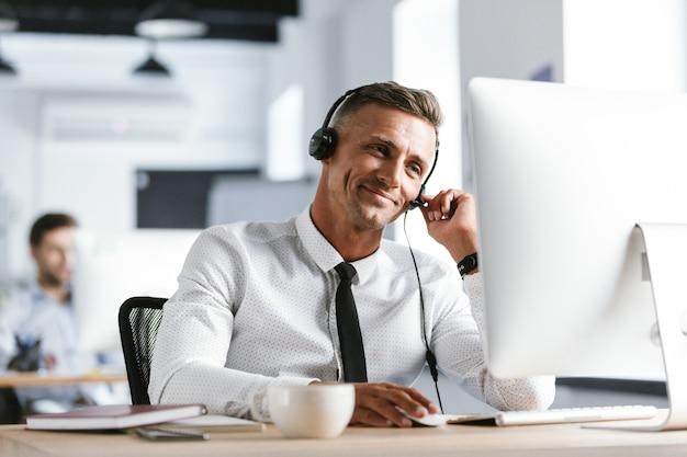 Foto des freudigen betreibermannes 30s, der bürokleidung und headset trägt, lächelnd, während er am computer im callcenter arbeitet