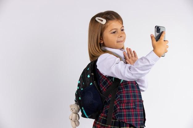 Foto des freudigen hübschen blonden schulmädchens, das selfie auf mobiltelefon nimmt und hallo zeichen lokalisiert auf weißer wand mit freiem raum gestikuliert.