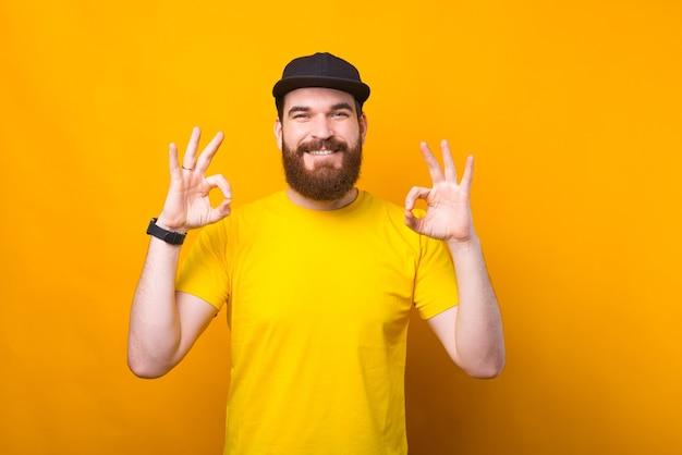 Foto des freudigen jungen mannes im gelben hemd, das ok-geste zeigt und in die kamera lächelt