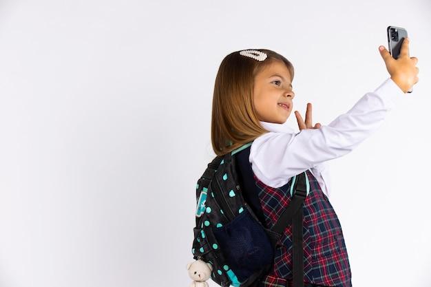 Foto des freudigen, lächelnden schönen schulmädchens, das selfie auf handy nimmt und friedenszeichen gestikuliert. isolierte weiße wand