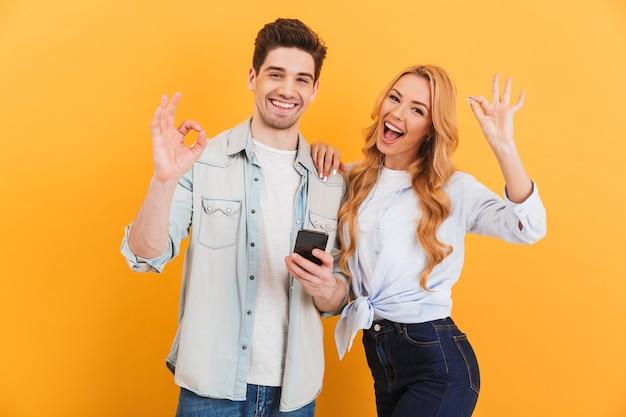 Foto des freudigen paares mann und frau lächelnd und zeigt ok zeichen beim halten des smartphones, lokalisiert über gelbe wand