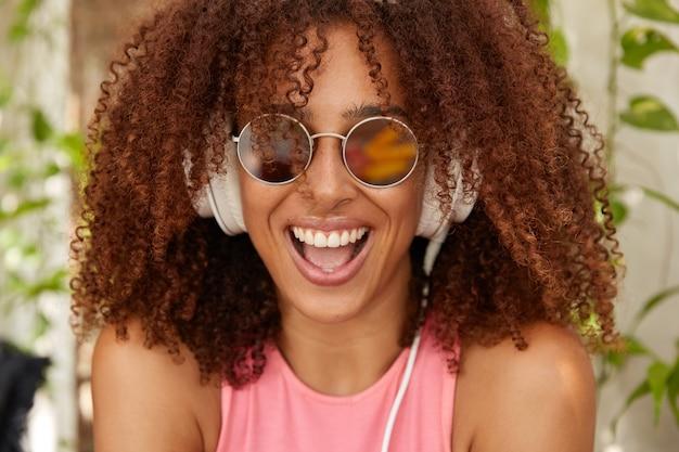 Foto des freudigen stilvollen teenagers mit afro-haarschnitt