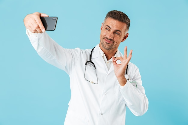 Foto des freundlichen arztes, der weißen kittel und stethoskop trägt, das selfie auf smartphone nimmt, lokalisiert über blauer wand