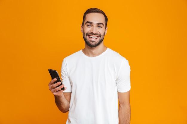 Foto des freundlichen mannes 30s in der freizeitkleidung lächelnd und hält smartphone, lokalisiert