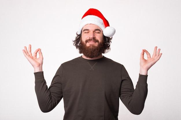 Foto des friedlichen bärtigen mannes, der weihnachtsmannhut trägt und zen-geste macht