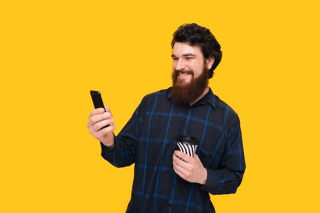 Foto des fröhlichen bärtigen mannes, der ein smartphone verwendet, während eine tasse mit kaffee hält