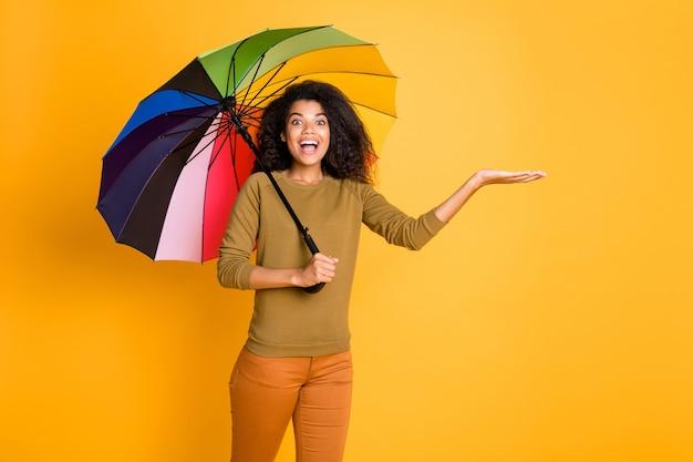 Foto des fröhlichen braunen positiven niedlichen netten netten charmanten hübschen süßen mädchens, das objekt mit händen hält, während regentropfen, die hosenhose orange tragen, lokalisiert über gelbem lebendigem farbhintergrund fangen