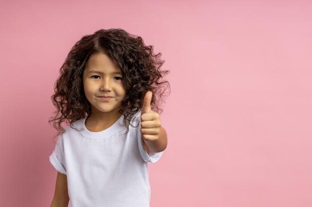 Foto des fröhlichen kleinen mädchens mit dunklem haar, brauner haut, das lässiges t-shirt tragend tut, okay geste macht, ihre zustimmung demonstrierend, lächelnd, isoliert. körpersprachenkonzept.