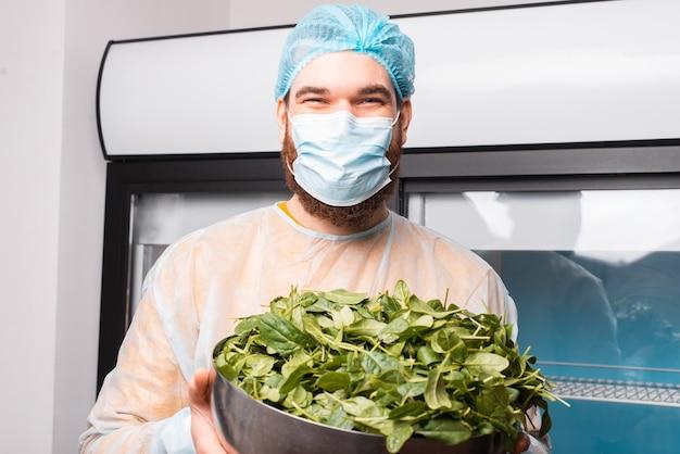 Foto des fröhlichen kochmanns, der schüssel mit spinat hält