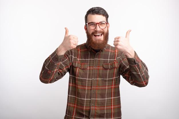 Foto des fröhlichen mannes, der brille trägt und daumen hoch geste über leerraum zeigt