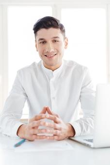 Foto des fröhlichen mannes im weißen hemd gekleidet. coworking. blick in die kamera.