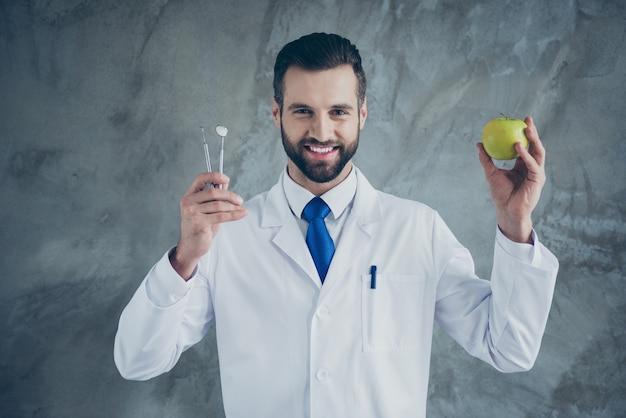 Foto des fröhlichen positiven arztes, der instrumente und apfel hält, der weißen mantel trägt, der zahnlos isolierte graue farbe betonwandwand lächelt