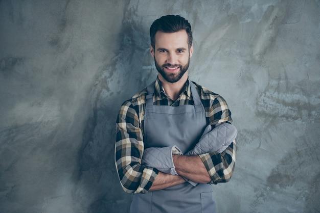 Foto des fröhlichen positiven kochs, der spaßruhe nach hartem arbeitstag trägt, der handschuhe kariertes hemd mit zahnigem lächeln isolierte graue wandbetonfarbwand trägt