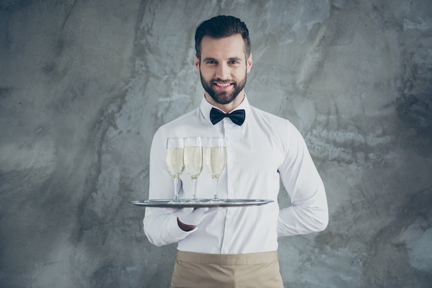 Foto des fröhlichen positiven zahnigen strahlenden kellners, der tablett mit gläsern des funkelnden getränks hält, lokalisiert über graue betonwand