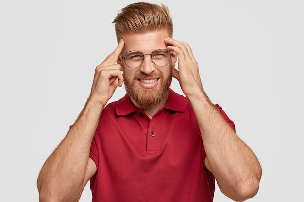 Foto des fröhlichen rothaarigen jungen hipsters hat schlechtes gedächtnis, hält hände an schläfen, versucht sich an etwas zu erinnern, hat freundliches lächeln, trägt lässiges outfit, steht allein gegen weiße wand.