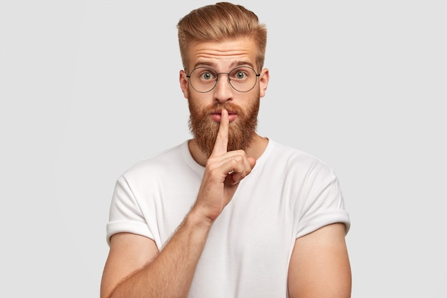 Foto des geheimen ingwer stilvollen männlichen kerls zeigt schweigezeichen, hat ausdruck überrascht, afraids des enthüllens des geheimnisses, lässig gekleidet, posiert allein gegen weiße wand. menschen- und geheimhaltungskonzept