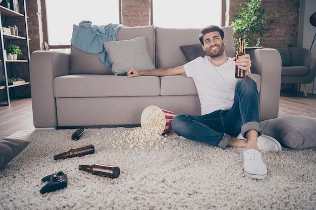 Foto des gemischten rassen-kerls, der teppich nahe sofa sitzt, der bierflasche-popcornboden hält, der spaß verrückte junggesellenabschied hat, stört unordentliche schmutzige wohnung, die beste freundgäste drinnen trifft