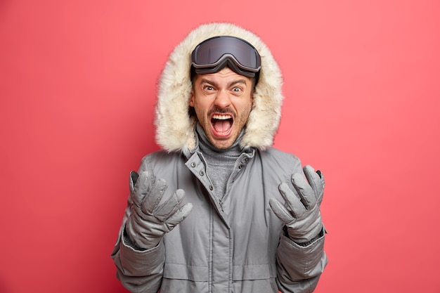 Foto des gereizten europäischen mannes schreit laut und gesten drücken wütend negative gefühle aus, trägt warme thermojackenhandschuhe.