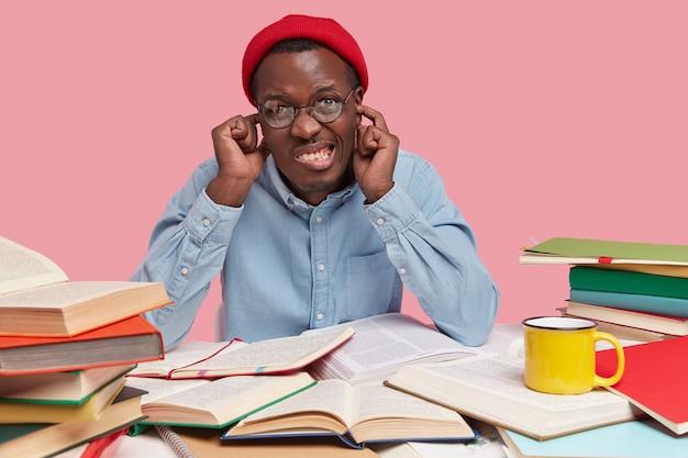 Foto des gereizten schwarzen mannes biss die zähne zusammen, stopft die ohren mit beiden zeigefingern, gekleidet in roten hut und hemd