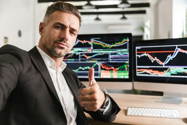Foto des geschäftsmäßigen mannes 30s, der anzug trägt, der selfie nimmt, während im büro am computer mit grafiken und diagrammen am bildschirm arbeitet