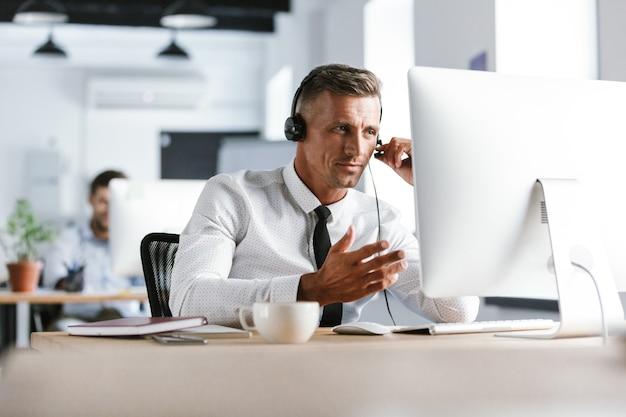 Foto des geschäftsmäßigen mannes 30s, der bürokleidung und headset trägt und am computer im callcenter sitzt