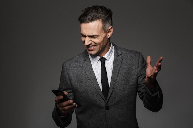 Foto des geschäftsmäßigen mannes, der geschäftskostüm trägt, das empörung und ressentiments ausdrückt, während handy im büro benutzt, lokalisiert über graue wand