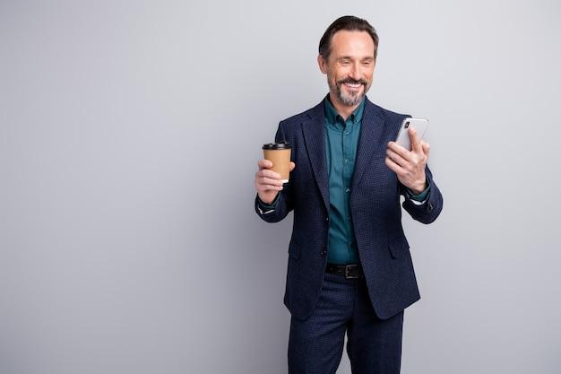 Foto des geschäftsmannes halten kaffeetasse zum mitnehmen, die auf smartphone chattet