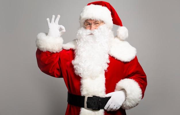 Foto des glücklich lächelnden weihnachtsmanns wirft auf
