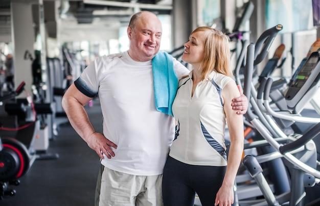 Foto des glücklichen älteren ehepaares in der turnhalle. umarmt und schaut in die kamera