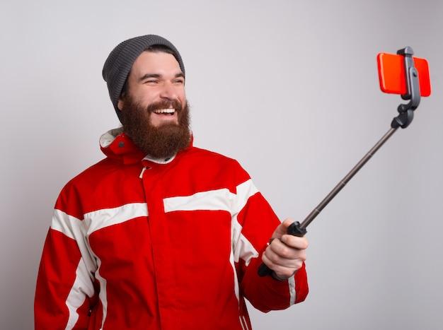 Foto des glücklichen bärtigen alpinisten, der selfie mit smartphone nimmt
