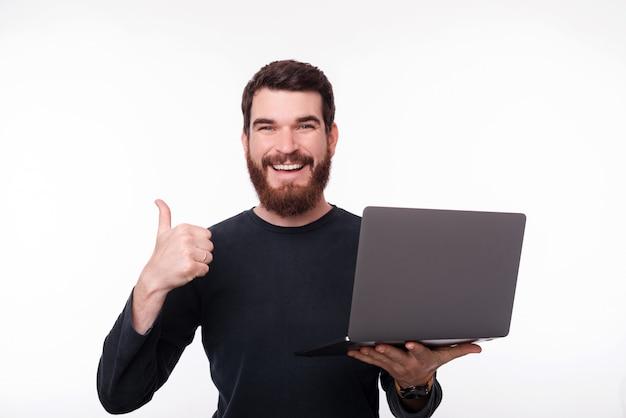 Foto des glücklichen bärtigen kerls, der einen laptop beim betrachten der kamera und des schuhs daumen uo, über weißem lokalisiertem hintergrund hält