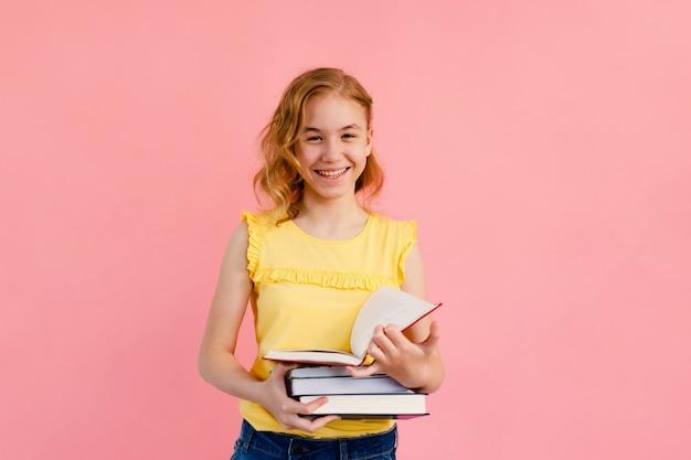 Foto des glücklichen charmanten blonden mädchens, das mit übungsbüchern aufwirft und über rosa hintergrund lokalisiert lächelt