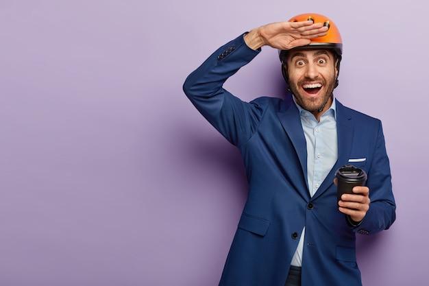 Foto des glücklichen europäischen kerls hält handfläche nahe stirn, trinkt kaffee zum mitnehmen, trägt kopfbedeckung und formellen anzug, versucht, etwas in die ferne zu sehen