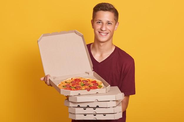 Foto des glücklichen freudigen mannes, der burgunderfarbenes lässiges t-shirt trägt, lächelnd in die kamera schaut und pizzaschachteln hält