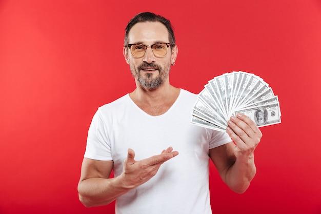 Foto des glücklichen gewinnermannes im lässigen weißen t-shirt lächelnd und demonstrierend fan des geldes in dollar-banknoten, die in der hand halten, lokalisiert über roter wand