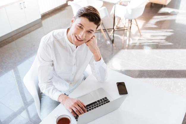 Foto des glücklichen jungen mannes, der im weißen hemd gekleidet wird, das nahe tasse kaffee und telefon sitzt, während er laptop-computer verwendet. coworking. blick in die kamera.