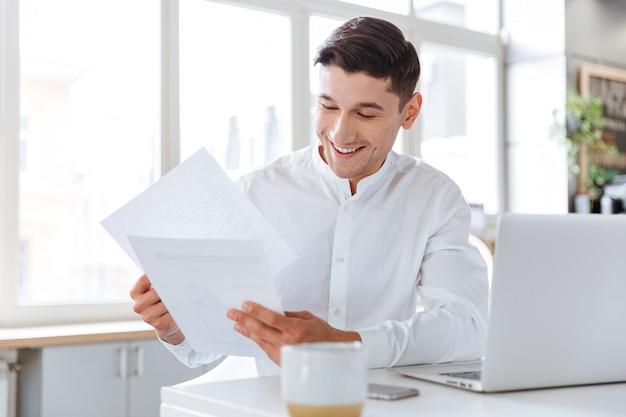 Foto des glücklichen jungen mannes kleidete im weißen hemd an, das dokumente während der verwendung des laptop-computers hält. coworking. dokumente anschauen.
