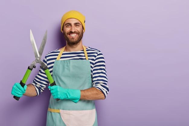 Foto des glücklichen jungen mannes mit fröhlichem ausdruck, hält gartenschere für das beschneiden von pflanzen, hat lächeln auf gesicht, gekleidet in arbeitskleidung, arbeitet im garten