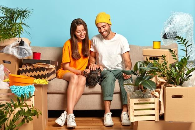 Foto des glücklichen jungen paares, das auf der couch sitzt, umgeben von kisten