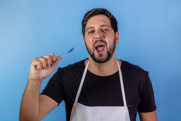 Foto des glücklichen kochmanns, der utensil für das kochen von fleisch hält