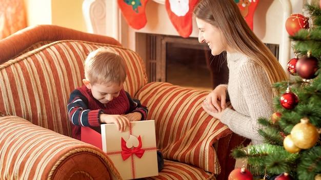 Foto des glücklichen lächelnden kleinen jungen öffnet kasten mit weihnachtsgeschenk und schaut nach innen. mutter, die ihrem kind zu neujahr ein geschenk gibt