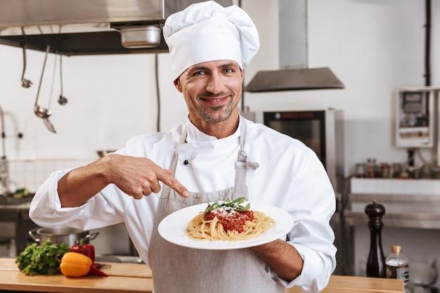 Foto des glücklichen männlichen chefs in der weißen uniform, die platte mit mahlzeit hält