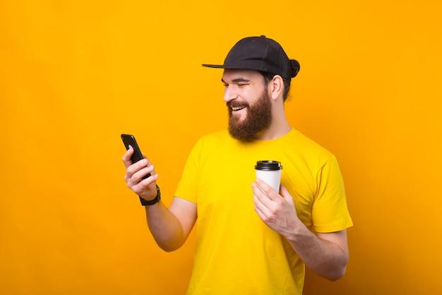 Foto des glücklichen mannes, der eine pause vom job hat, der kaffee trinkt und telefon benutzt