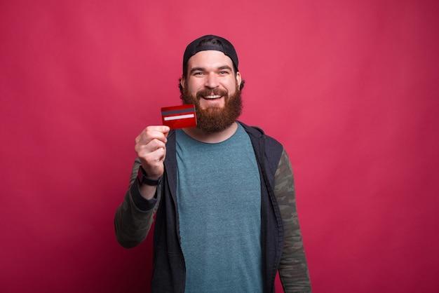 Foto des glücklichen mannes, der seine neue kreditkarte zeigt