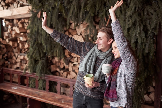 Foto des glücklichen mannes und der hübschen frau mit den schalen im freien im winter. winterurlaub und ferien. weihnachtspaare des glücklichen mannes und der frau trinken heißen kaffee. hallo nachbarn