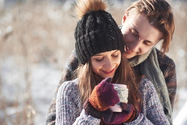 Foto des glücklichen mannes und der hübschen frau mit den schalen im freien im winter. winterurlaub und ferien. weihnachtspaare des glücklichen mannes und der frau trinken heißen wein. verliebtes pärchen