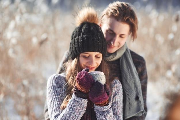 Foto des glücklichen mannes und der hübschen frau mit tassen im freien im winter. winterurlaub und urlaub. weihnachtspaar des glücklichen mannes und der frau trinken heißen wein. verliebtes pärchen