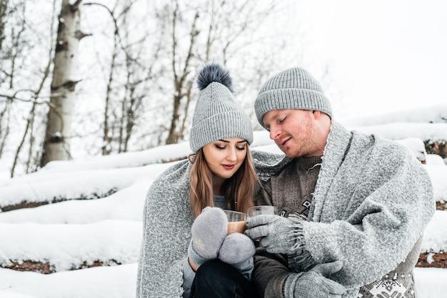 Foto des glücklichen mannes und der hübschen frau mit tassen im freien im winterurlaub und im urlaub. weihnachtspaar verliebt.